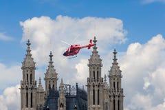Flygambulanshelikoptern flyger över den Westminster slotten, London (UK) Royaltyfri Fotografi