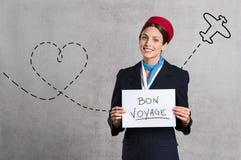 Flygassistent som önskar Bon Voyage arkivbilder