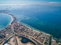 Flygbild av byggnader, villor och stranden på ett naturligt som spottas av La Manga mellan det medelhavs- och Mars Menor, fotografering för bildbyråer