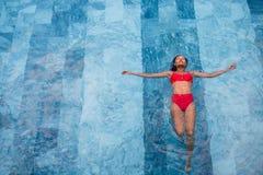 Flygbilden för den bästa sikten av en förförisk sexig modell i vit swimwear tycker om kopplar av i hotellpöl under hennes sommar Arkivfoton