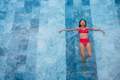 Flygbilden för den bästa sikten av en förförisk sexig modell i vit swimwear tycker om kopplar av i hotellpöl under hennes sommar Royaltyfri Fotografi