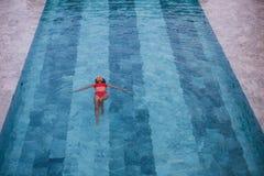 Flygbilden för den bästa sikten av en förförisk sexig modell i vit swimwear tycker om kopplar av i hotellpöl under hennes sommar Royaltyfri Bild