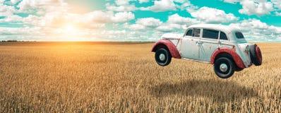 Flygbilen skjuta i höjden in i himlen Den Retro bilen svävar i luften ovanför ett guld- vetefält på bakgrunden av blå himmel royaltyfri foto