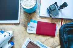 Flygbiljetter, pass, kamera, minnestavla, jeans och ?versikt p? tabellen Samla f?r att en tur eller ett lopp ska m?ta aff?rsf?ret royaltyfri fotografi