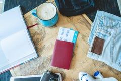 Flygbiljetter, pass, kamera, minnestavla, jeans och ?versikt p? tabellen Samla f?r att en tur eller ett lopp ska m?ta aff?rsf?ret royaltyfria foton