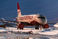 Flygbolag för vingar för Sukhoi Superjet som 100 röda parkeras på flygplatsen på natten Arkivbild