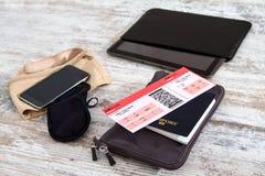 Flygbolagbiljett, pass och elektronik Arkivfoto