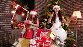 Flyggåvor nära julgranen från Santa Claus, älskvärda flickor staplar festliga askar, sexiga flickor i Santa Claus hattar lager videofilmer