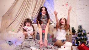 Flygkonfettier, mångfärgade flygkonfettier runt om flickvänner, den lyckliga familjen som applåderar, glade flickor, firar nytt å arkivfilmer
