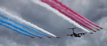 Flygparad av RAF Red Arrows som eskorterar en flygbuss A400M Royaltyfria Bilder