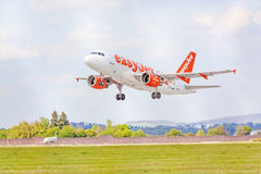 Flygplan av easyJet, innan att landa/efter starten, himmel med moln royaltyfri bild