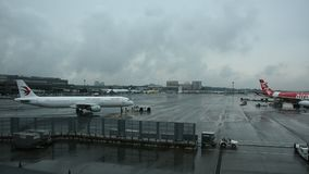 Flygplan boeing och det japanska folket förbereder nivån för tagande av och landning på landningsbana, medan regna i Narita den i lager videofilmer