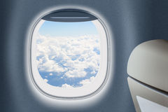Flygplan- eller strålfönster med moln bakom och att resa begrepp Arkivbild