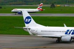Flygplan för UTair flygbolagBoeing 737-500 flygplan och för British Airways flygbuss A320-232 i Pulkovo den internationella flygp Royaltyfria Bilder