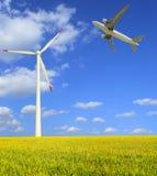 Flygplan flyger i turbinerna för vind för rislantgårdar de moderna Arkivbilder