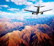 Flygplan i berglandskap Fotografering för Bildbyråer