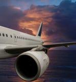 Flygplan i dramatisk sky över havet. Arkivfoto