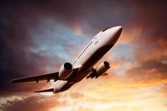 Flygplan i himlen på solnedgången arkivfoton