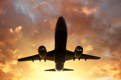 Flygplan i himlen på solnedgången arkivbilder