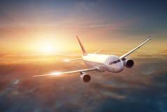 Flygplan i himlen på solnedgången royaltyfria foton