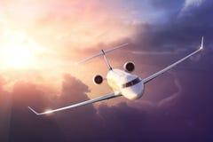 Flygplan i himlen på solnedgången Royaltyfri Bild