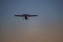 Flygplan i luften och solnedgånghimlen i bakgrund Royaltyfri Bild