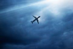 Flygplan i mörker - blå himmel och moln i strom Arkivfoton