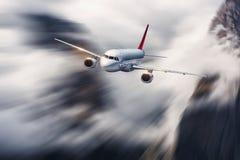 Flygplan i rörelse Flygplan med effekt för rörelsesuddighet flyger i moln mot berg flygplanbarn som tecknar passagerare s royaltyfria bilder