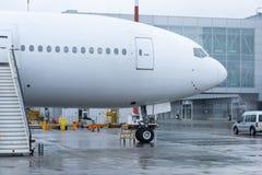 Flygplan med en stege p? den slutliga byggnaden f?r flygplats arkivfoto
