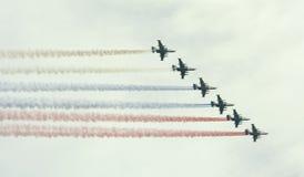 Flygplan med tricolor rökryss Arkivbilder