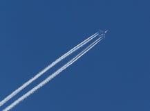 Flygplan och diagonala kondensationsslingor eller Contrails på blå himmel Arkivfoton
