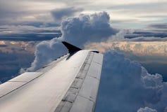 Flygplan ovanför oklarheter i skyen arkivfoto