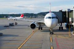 Flygplan på en flygplats med passagerarelandgången royaltyfri bild