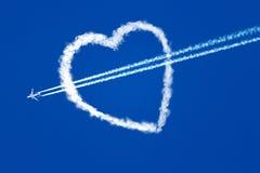 Flygplan på flyget för blå himmel till och med hjärtan av molnen Arkivbild