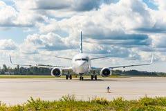 Flygplan på styrningspåret på flygplatsen, exakt i mitt i ramen, mot bakgrunden av en pittoresk himmel i th royaltyfria foton