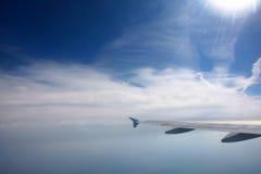 Flygplan påskyndar i skyen Arkivbild