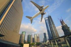 Flygplan som över flyger över de moderna stadsbyggnaderna Royaltyfri Fotografi