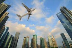 Flygplan som över flyger över de moderna stadsbyggnaderna Arkivfoto