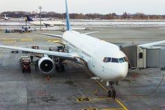 Flygplan som anslutas i flygplats Arkivbild