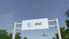 Flygplan som flyger över advertizingaffischtavlan med Amerikan Ringa och Telegrafera Företag PÅ T-logoen Ledare 3D Arkivfoton