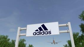 Flygplan som flyger över advertizingaffischtavlan med den Adidas inskriften och logoen Redaktörs- tolkning 3D Royaltyfri Bild