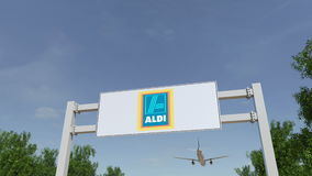 Flygplan som flyger över advertizingaffischtavlan med den Aldi logoen Redaktörs- tolkning 3D Royaltyfri Fotografi