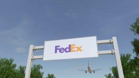 Flygplan som flyger över advertizingaffischtavlan med den Fedex logoen Redaktörs- tolkning 3D Arkivfoton