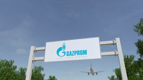 Flygplan som flyger över advertizingaffischtavlan med den Gazprom logoen Redaktörs- tolkning 3D Arkivfoto