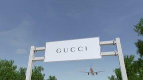 Flygplan som flyger över advertizingaffischtavlan med den Gucci logoen Redaktörs- tolkning 3D Arkivbild