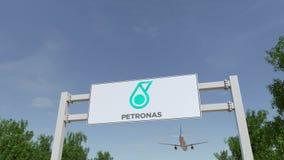 Flygplan som flyger över advertizingaffischtavlan med den Petroliam Nasional Berhad PETRONAS logoen Redaktörs- tolkning 3D Arkivfoto