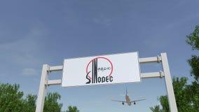 Flygplan som flyger över advertizingaffischtavlan med den Sinopec logoen Redaktörs- tolkning 3D Arkivbild