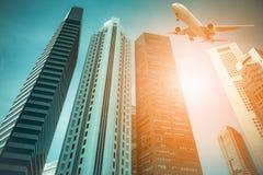Flygplan som flyger över de moderna stadsbyggnaderna i Singapore Arkivfoto
