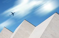 Flygplan som flyger över modern byggnad royaltyfri bild