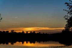 Flygplan som flyger över sjön på solnedgången Royaltyfria Bilder